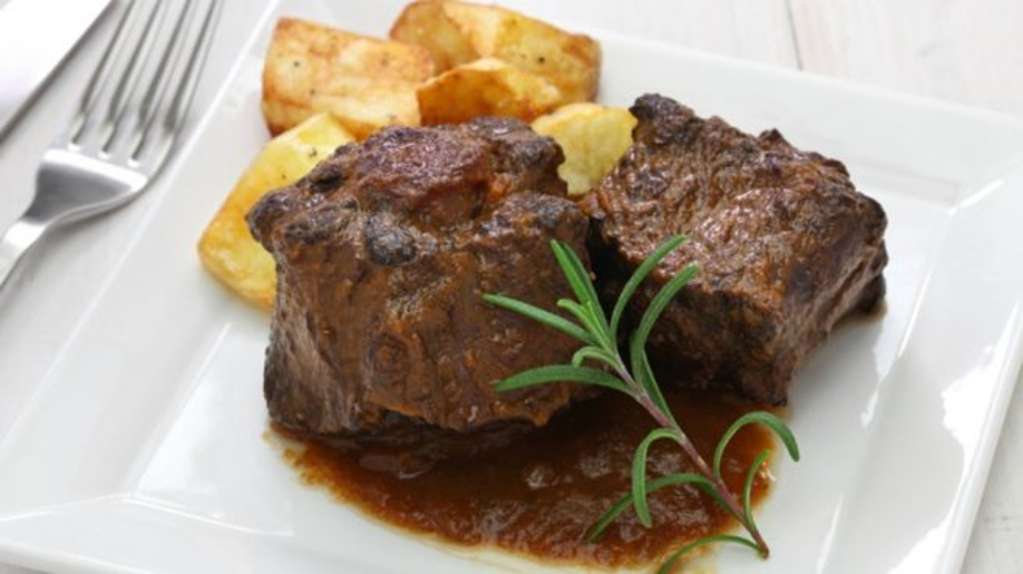 bull's tail (rabo de toro) accompanied with potatoes on a plate, one of the most delicious spanish food